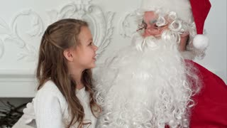 Sweet little girl sitting on Santa lap and describing him what she ...