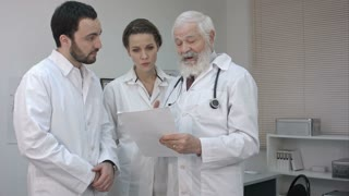 Team Of Experts Doctors Looking At Hospital Report.