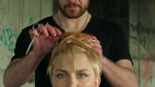 The master does a hairdress to a blond girl