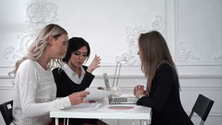 Three business women working in the office and discussing something