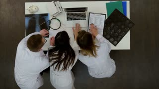 Three concentrated doctors using laptop in the office