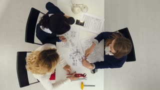 Three female engineers working on plans at business boardroom table