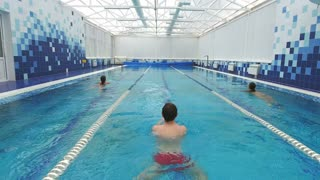 Three young people swimming in different pool lanes