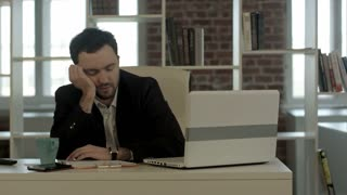 Tired businessman sleeping in office, wake up and start talking phone