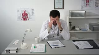 Tired doctor at medical cabinet