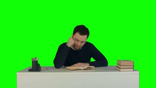 Tired man reading a book in a library on a Green Screen