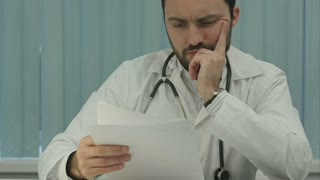 Tired medical doctor tired from paper work with documents