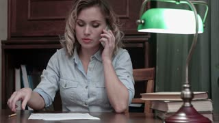 Tired young woman sitting at her desk receiveing very bad news on the phone