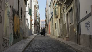 Together in an old street, old couple walking throught Lisbon street