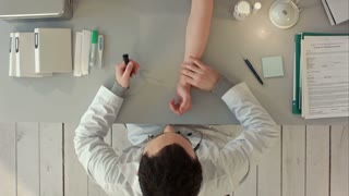 Top view of The doctor measures pulse at the patient