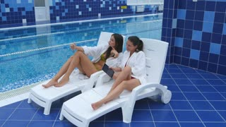 Two beautiful girls taking selfies next to swimming pool