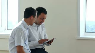 Two business executives sitting in a bright office space, looking for information together by sharing the screen of a digital tablet