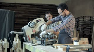 Two carpenters works on woodworking machine in workshop