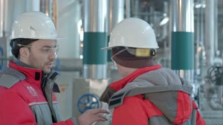 Two chemical factory workers having conversation in plant