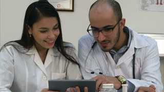 Two doctors looking at something funny on the tablet and laughing