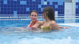 Two happy female freinds enjoying jacuzzi in the swimming pool