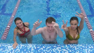 Two happy young women and a young man having fun in the swimming pool