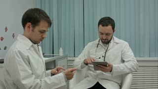 Two male doctors at medical cabinet using mobile phones