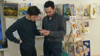 Two young men using smartphone in art class