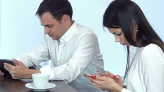 Two young people in cafe busy working with their phone and tablet
