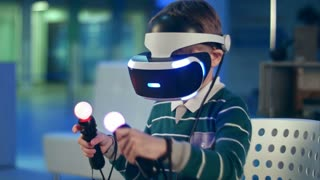 Active little boy enjoying virtual reality with motion controllers in his hands