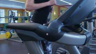 Active young woman running on treadmill in sport club
