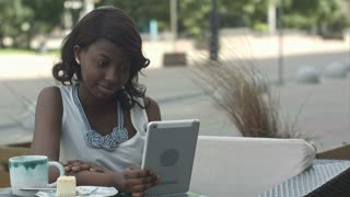 African american woman have video conferance on her tablet sitting in outside cafe