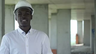 African worker at construction site talking and looking at camera