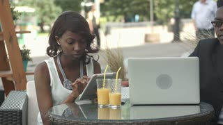 Afro-american business man and woman working together in modern cafe, having phone calls, using laptop and digital tablet