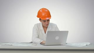 Angry female engineer in hardhat with documents in stress because of result on white background