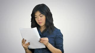Asian business women looking document file in her hand on white background