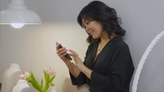 Asian woman looking at smartphone screen and smiling in a living room