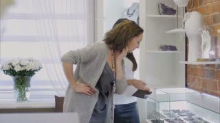 Attractive woman and female seller consultant looking on jewellery through the showcase