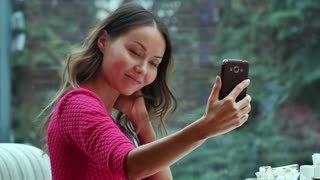 Attractive woman taking self portrait by mobile phone in cafe