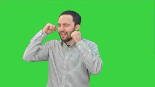 Bearded young man happily dancing and singing on a Green Screen, Chroma Key