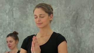 Beautiful blond woman praying or practising yoga at home, holding hands in namaste