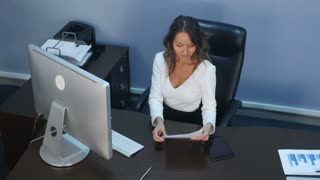 Beautiful business lady working with digital tablet and documents in office