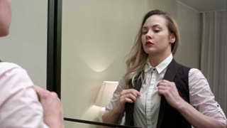Beautiful businesswoman getting ready to leave putting a vest on, checking her self out in the mirror
