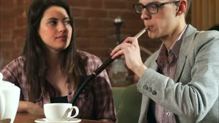 Beautiful couple smokes hookah and talk in the bar