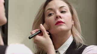 Beautiful girl looking in the mirror and applying cosmetic with a big brush