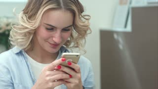 Beautiful smiling woman texting on smartphone in beauty salon