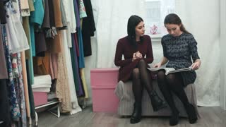 Beautiful young woman in fashion atelier haute couture talking with desighner, flipping through a magazine, discussing new dress for customer