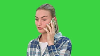 Beautiful young woman talking on mobile phone seriously on a Green Screen, Chroma Key