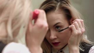 Beauty teenage girl applying mascara and admiring herself in the mirror