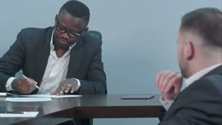 Black businessman signs a contract and gives papers to a partner