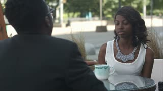Black girl with holding a cup of coffee, talking to her afro american colleague, sitting outside cafe