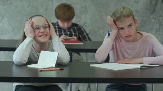 Bored girl sitting at desk in school classroom, discussing something with classmate
