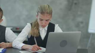 Business children working with documents and with laptop