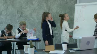 Business children writing on flipchart in office