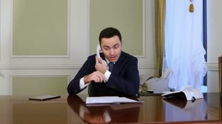 Businessman having trouble while phoning and puts the phone down